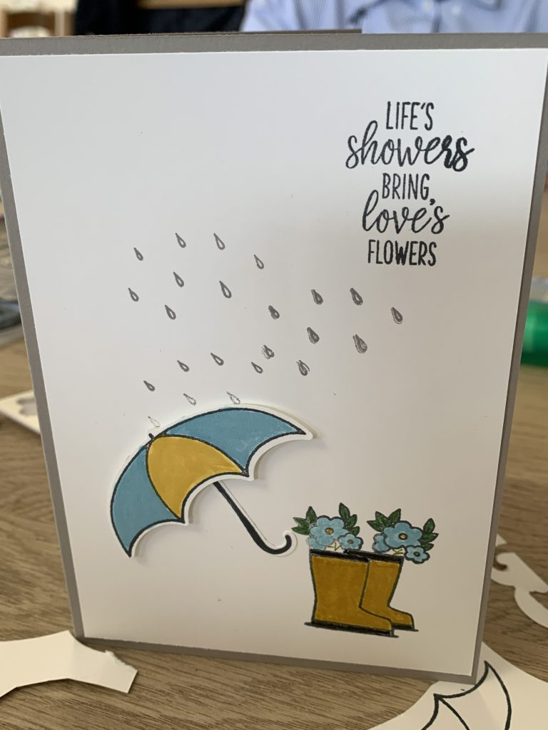 Under My Umbrella card using #simplestamping for Coffee and  Cards. This one had a rain shower, shimmery boots in Coastal Cabana with flowers tumbling out of the top.