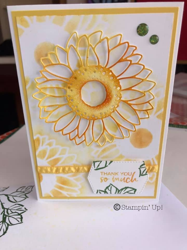 Hand made card featuring a soft background of sunflowers and  a sunflower die coloured with Daffodil Delight ink using blending brushes. All products from Stampin' Up!